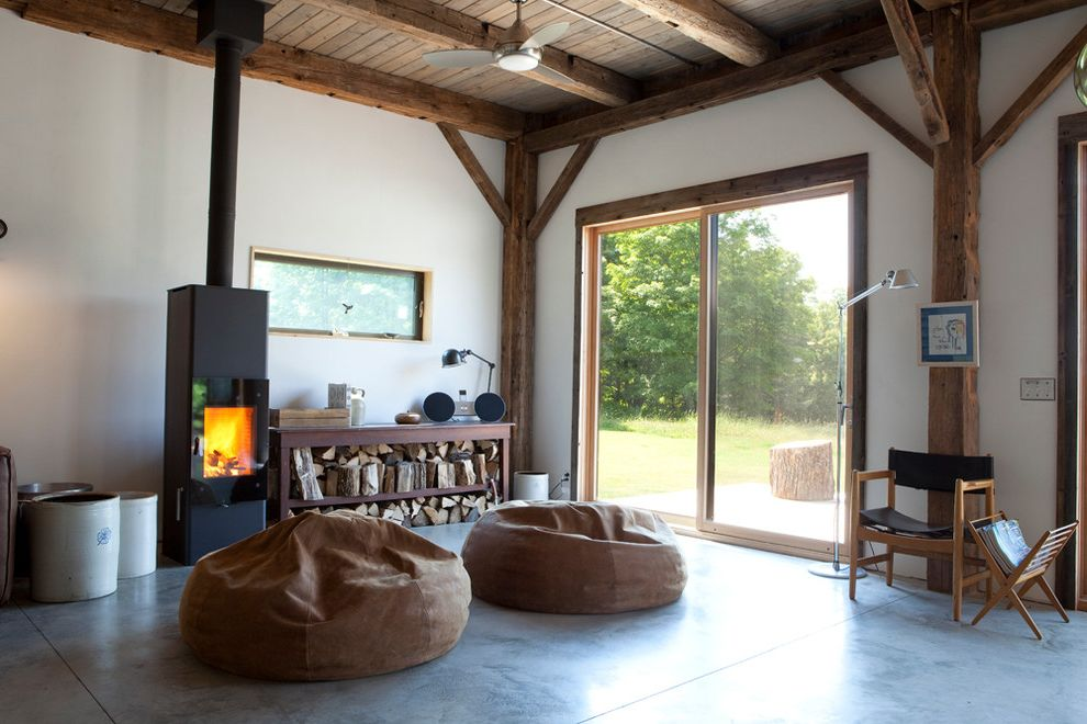 Conduction Stove   Rustic Living Room Also Bean Bag Chairs Cabin Ceiling Fan Concrete Flooring Exposed Beams Firewood Storage Magazine Storage Reading Lamp Rustic Sliding Glass Doors Wood Ceiling Wood Stove