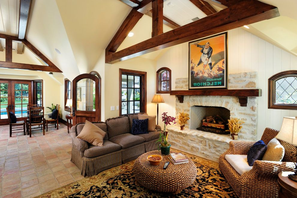 Construction Companies in Phoenix with Traditional Living Room  and Area Rug Exposed Beams Fireplace Hearth Floor Tile Great Room Oriental Rug Sloped Ceiling Stone Fireplace Surround Vaulted Ceilings Vintage Poster Wall Art Wall Decor Wood Molding