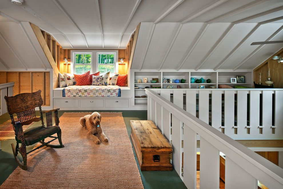Convert Attic to Loft with Farmhouse Family Room  and Cabin Camp Style Decorative Pillows Green Flooring Lake Home Lake House Lodge Open Shelving Retreat Rocking Chair Sloped Ceiling Storage Chest Vacation Wall Sconces White Railing Window Seat