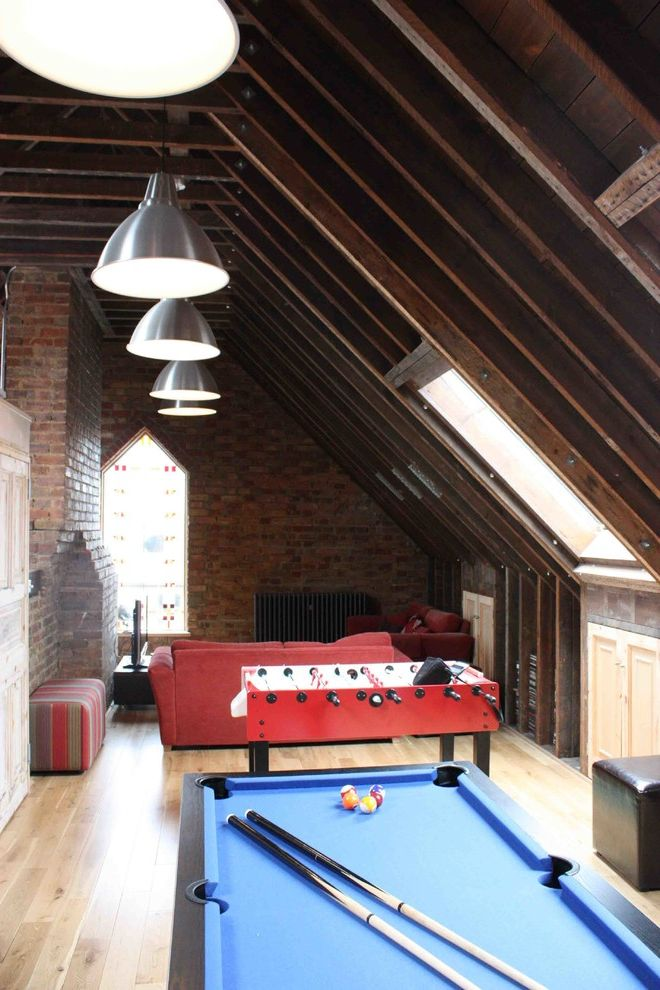 Convert Attic to Loft with Industrial Family Room Also Area Rug Attic Bar Billiards Brick Wall Built in Cabinetry Foosball Funky Teen Bedroom Game Room Light Wood Floors Man Cave Pendant Light Pool Table Skylight Sloped Ceiling Sofa Window Wood Beams
