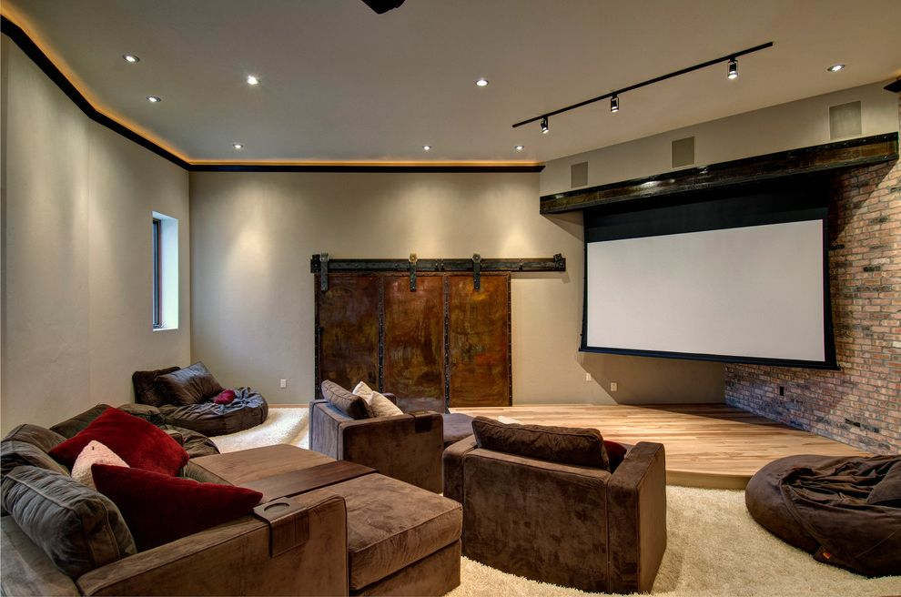 Copper Creek Theater with Contemporary Home Theater  and Brick Wall Brown Armchairs Ceiling Lighting Gray Walls Home Theater Projector Screen Recessed Lighting Sliding Barn Door Stadium Seating Stage