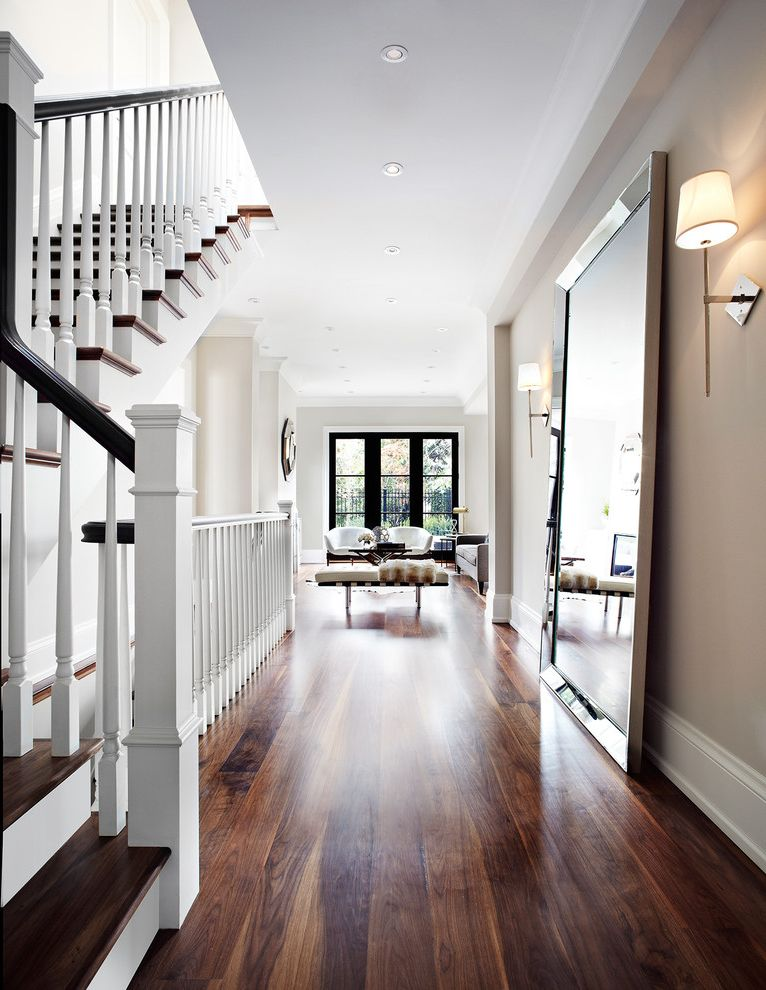 Coretec Flooring Reviews with Transitional Hall  and Beige Wall Foyer Full Length Mirror Glass Doors Landing Living Room Neutral Recessed Lighting Wall Sconces White Banister White Risers White Trim Wood Floors Wood Handrail Wood Tread