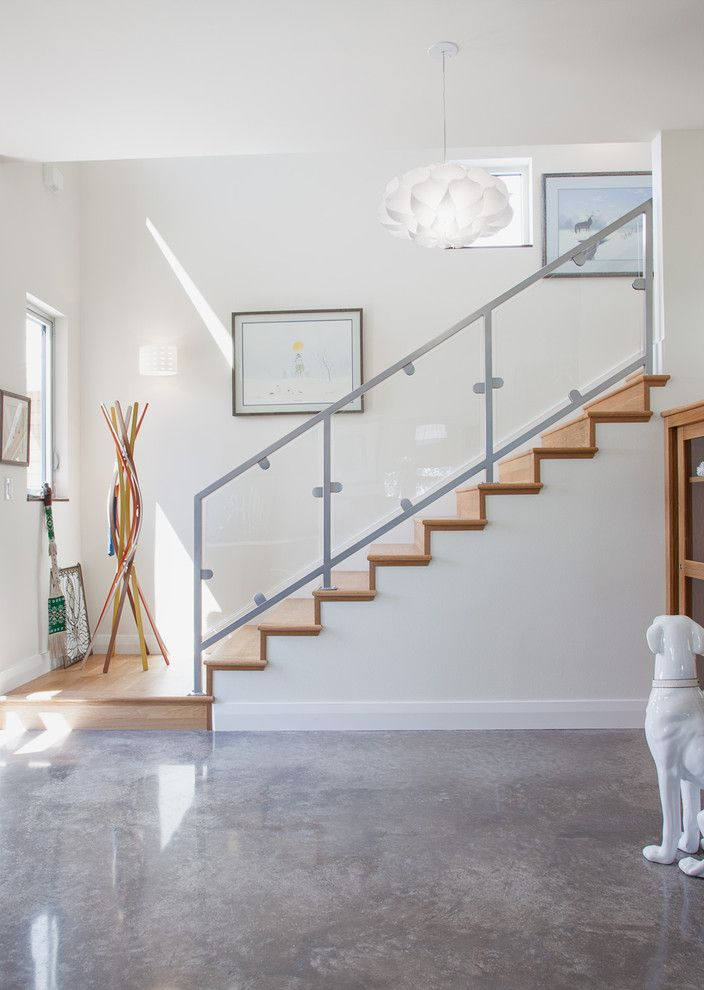 Cortex Plus Flooring with Contemporary Entry  and Art Wall Ceramic Dog Concrete Floor Glass Railing Metal Railing Modern Coatrack Photo by Kailey J Flynn Photography Staircase White Pendant Light Wood Stairs