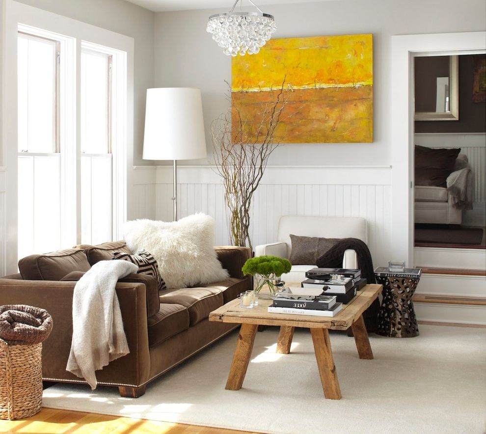 Couch with Studs   Rustic Living Room  and Accent Tables Area Rug Brown Sofa Double Hung Windows Gray Walls Nail Head Detail Rustic Table Lamp Wainscot White Casing Wicker Basket Wood Coffee Table Wood Floor Yellow Artwork