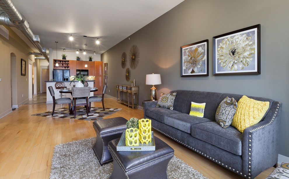Couch with Studs with Contemporary Living Room Also Dark Gray Ottoman Dark Gray Sofa Dining Room Gray and Yellow Color Scheme Gray Wall Great Room Kitchen Light Gray Shag Rug Light Wood Floor Narrow Room Track Lighting Yellow Accent Yellow Pillow