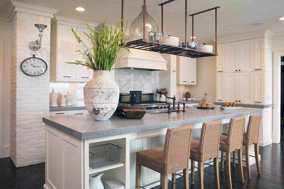 Countertops Jacksonville Fl with Traditional Kitchen  and Breakfast Bar Dark Floor Demijohn Eat in Kitchen Hanging Pot Rack Kitchen Island Range Hood Shaker Style White Brick White Kitchen Wire Basket Wood Flooring Woven Barstools