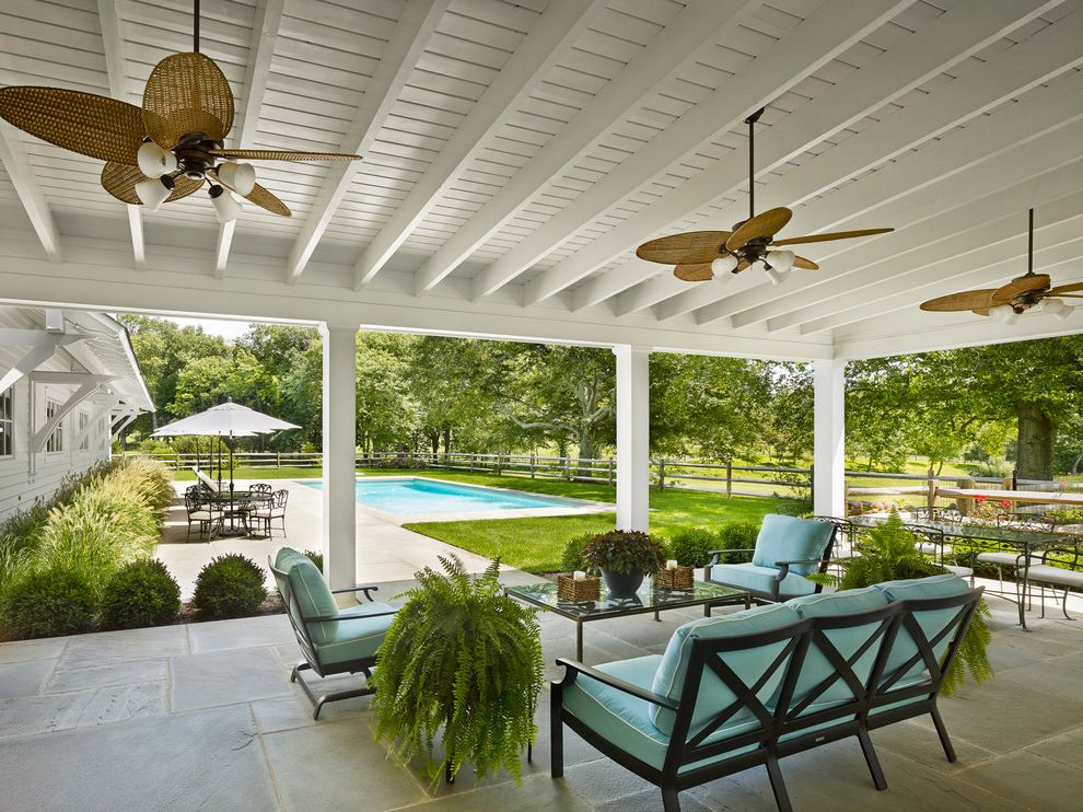 Covered Patio Kits with Farmhouse Patio  and Coffee Table Glass Top Covered Patio Farmhouse Painted Ceiling Palm Frond Ceiling Fan Potted Fern Rustic Fence Tile Floor Turquoise Cushions White Beams White Ceiling Wood Fence