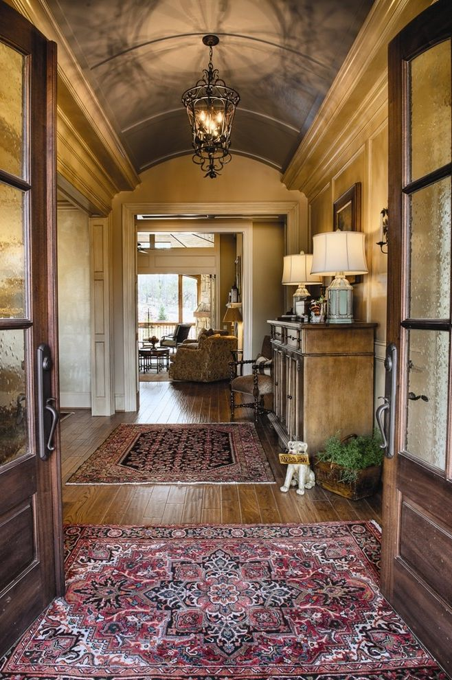 Crate and Barrel Two with Traditional Entry  and Barrel Vault Ceiling Crown Molding Dark Stained Sideboard French Doors Front Door Handlesets Molding Red Oriental Rug Red Persian Rug Two Table Lamps Wood Panel Walls Wrought Iron Pendant Light