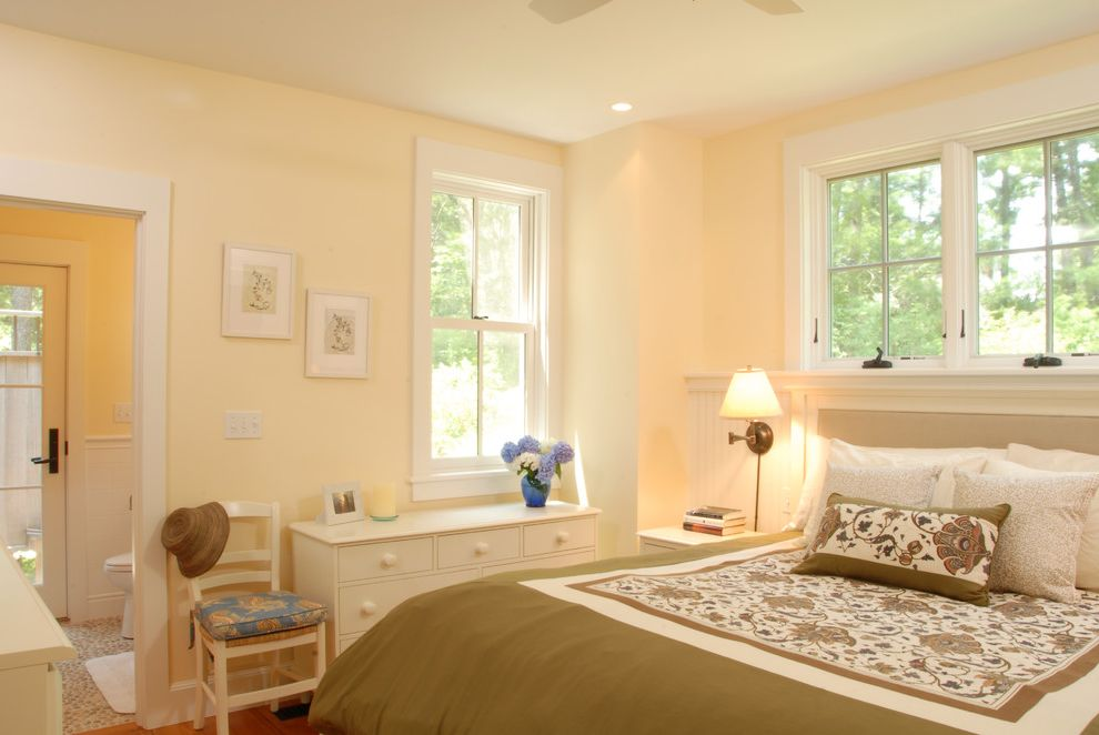 Cream Colored Comforter Sets with Traditional Bedroom Also Beadboard Butter Cottage Dresser en Suite Recessed Lights Rush Seat Sage Green Side Chair Wainscot Wall Sconce White Painted Wood White Trim Wood Floor Yellow