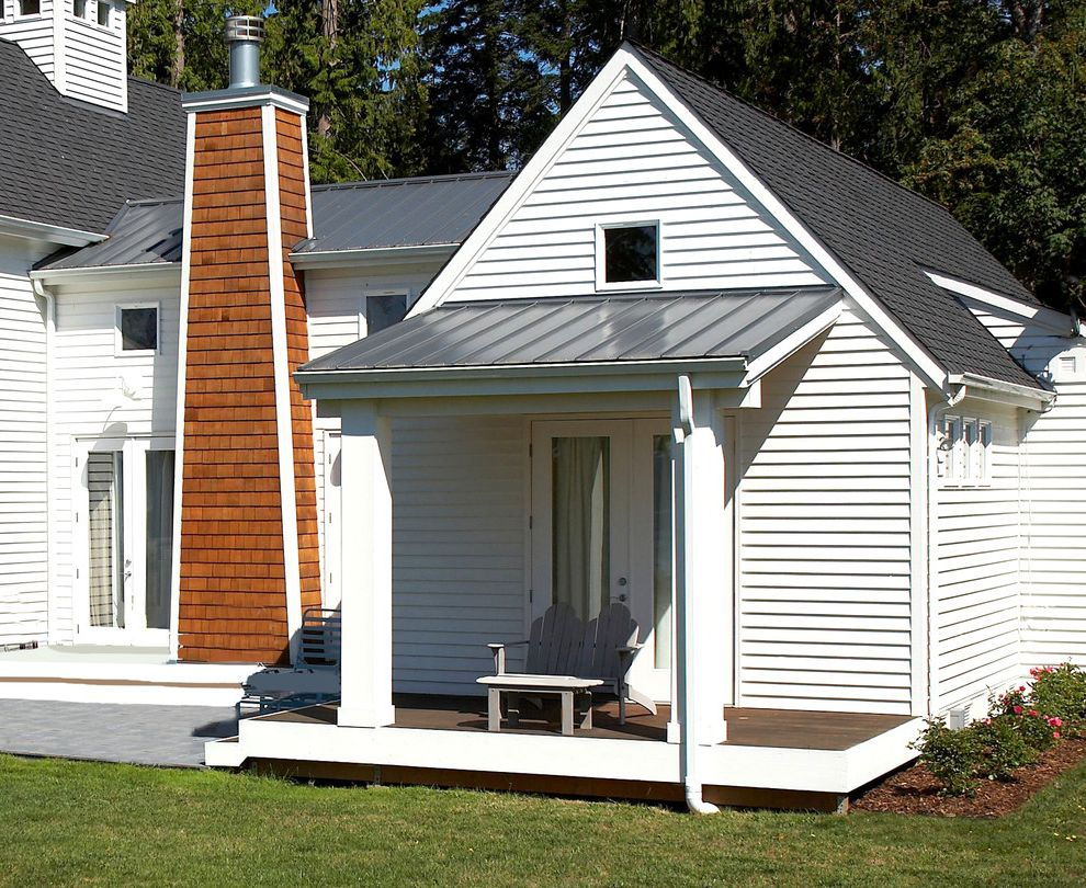 Crippen Sheet Metal with Eclectic Porch  and Adirondack Chair Cedar Shingle Chimney Covered Porch Cupola French Doors Gable Roof Grass Lawn Metal Roof Outdoor Seating Patio Pavers Porch White Lap Siding Wood Deck