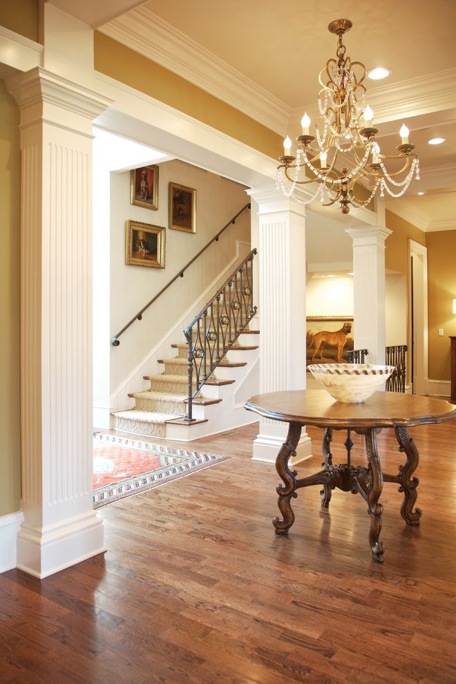 Deans Carpet with Traditional Hall and Beige Chandelier Crown Molding Dog Paintings Fluted Columns Gold Frames Iron Stair Railing Round Entry Table Stair Runner Tray Ceilings White Trim Wood Floor