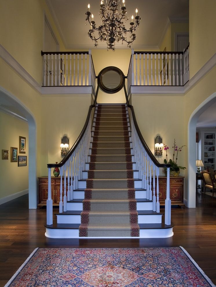 Deans Carpet with Traditional Staircase and Black Chandelier Console Crystal Chandelier Foyer Grand Staircase Mirrored Sconce Orchid Oriental Rug Round Mirror Runner Sconce White Spindles Wood Banister Wood Railing