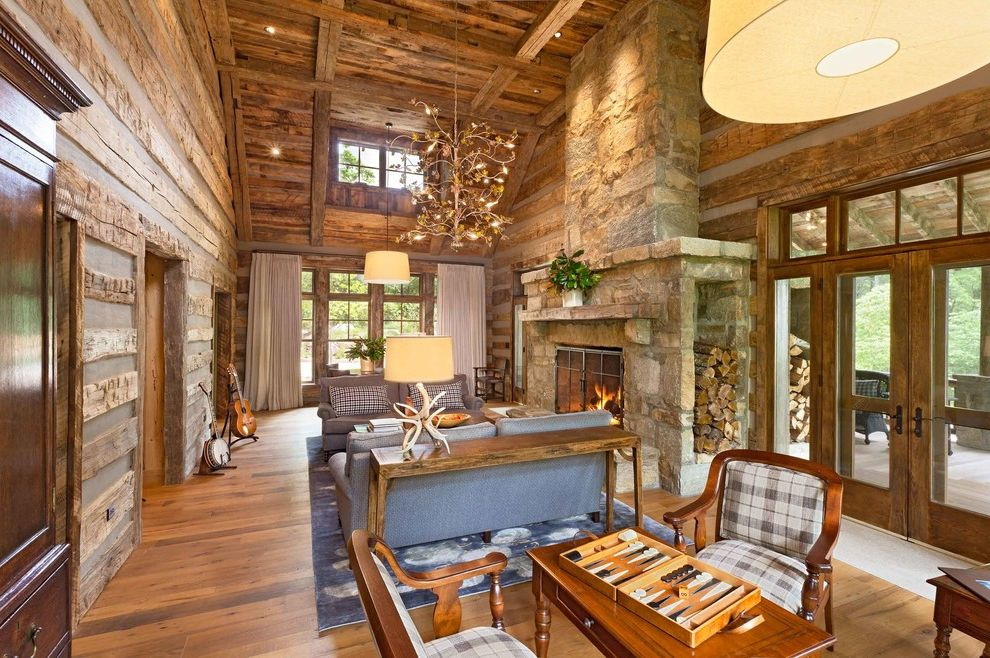 Deer Creek Storage   Rustic Living Room  and Area Rug Backgammon Chandelier Chinking Curtain Panels Fire Screen Fireplace Firewood Storage Guitar Stand Mantel Plaid Sofa Timber Frame Transom Window French Doors Vaulted Ceiling Wood Floor