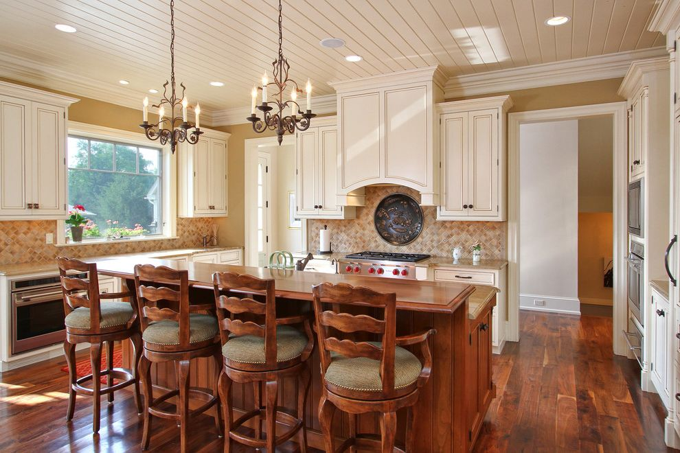 Different Color Wood Floors   Traditional Kitchen Also Beadboard Ceiling Beige Tile Backsplash Crown Molding Dark Wood Floors Eat in Kitchen Kitchen Island Painted Ceiling Plaque Two Chandeliers Wood Bar Stools Wood Countertop