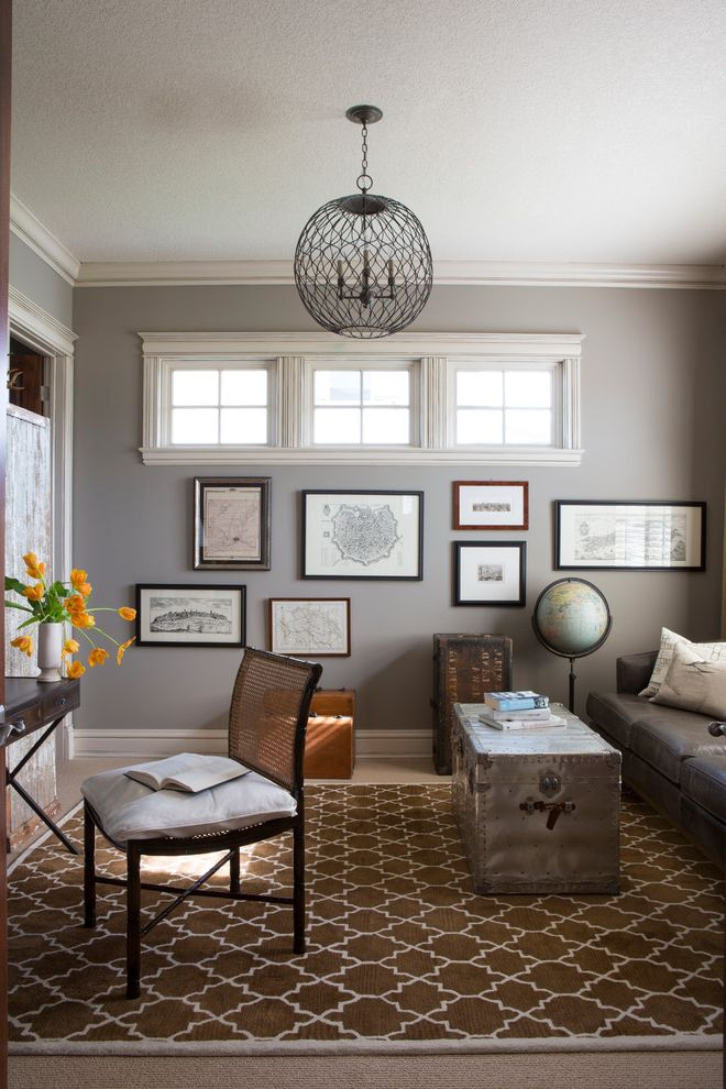 Dorian Gray Painting with Contemporary Home Office Also Brown Rug Cane Back Chair Chest Eclectic Decor Framed Maps Geometric Pattern Rug Globe Gray Wall Metal Trunk Neutral Color Scheme Orange Flowers Suitcases Trunk White Molding White Trim World
