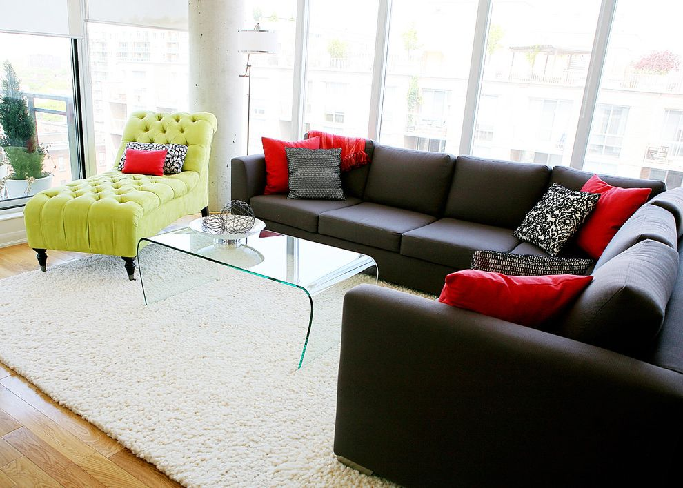 Dual Chaise Sectional   Contemporary Living Room  and Area Rug Black Sectional Concrete Column Glass Coffee Table Grey Grey Sectional Lime Green Chaise Printed Pillows Red Pillows Shag Rug Tall Windows White Walls Wood Floor