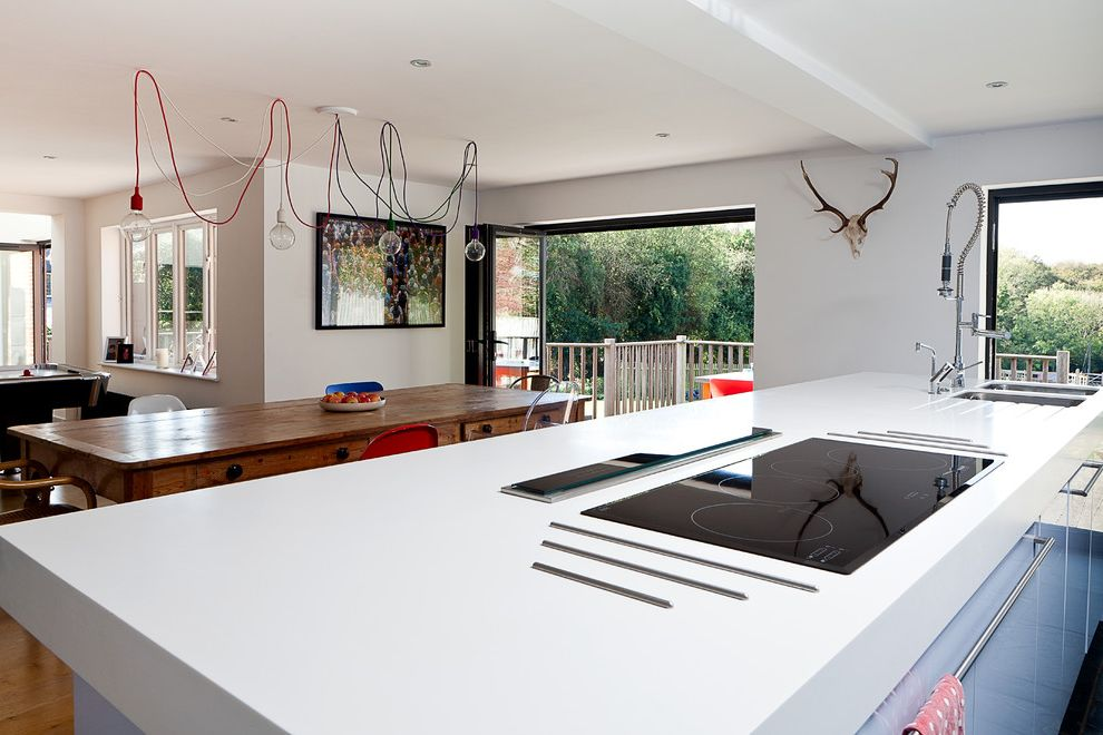 Electric Cooktop with Downdraft   Contemporary Kitchen  and Bi Fold Doors Blue Kitchen Cabinets Ceiling Light Corian Worktop Kitchen Island Open Plan Sink White Countertop Wood Table