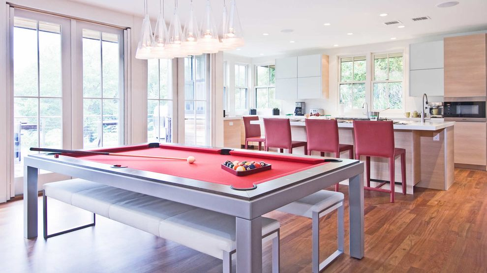 Elliptical Pool Table with Contemporary Kitchen  and Bench Seats Contemporary Pool Table Counter Stools Flush Cabinets Kitchen Island Pendant Lights Recessed Lights Red Tall Windows White Counters Wood Floor
