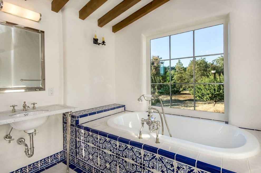 Emil Ceramica Tile   Mediterranean Bathroom Also Blue Tiles Hand Painted Tiles Large Window Marble Counter Mirror Cabinet Soaking Tub Tile Floor Wall Sconce Wall Mounted Sink Washstand White Stucco White Walls Wood Beams