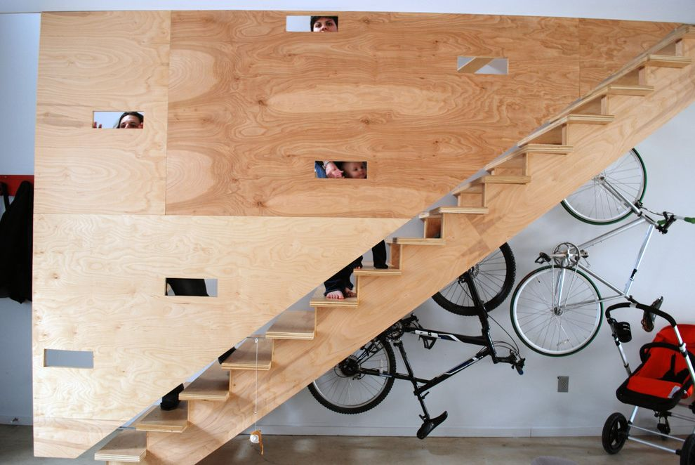 Energy Solutions Oakland with Industrial Staircase  and Accent Wall Bike Racks Concrete Flooring Industrial Loft Minimal Plywood Wall Under Stairs Storage Wood Staircase