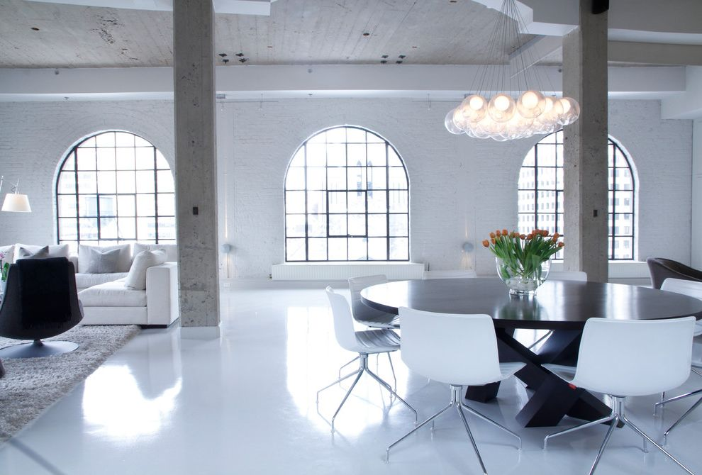 Epoxy Floors in Homes   Industrial Living Room  and Arched Windows Area Rug Chandelier Cluster Pendant Lights Concrete Columns Industrial Loft Open Painted Brick Round Dining Table Steel Windows White High Gloss Floors White Sofa