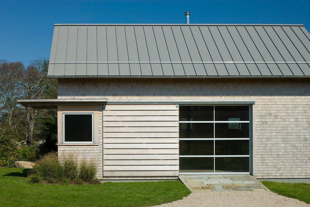 Estes Roofing with Modern Garage and Cedar Shake Eaves Exterior Glass Garage Door Grasses Gravel Landscape Lawn Mass Planting Metal Roof Shingle Siding Sliding Barn Door Stone Pavers Wood Trim