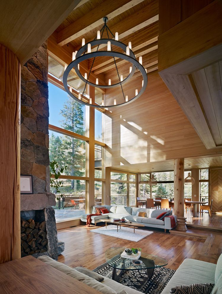 Expensive Chandeliers   Rustic Living Room  and Exposed Beams Gray Sectional Sofa High Ceiling Indoor Outdoor Living Iron Chandelier Living Space Mountain Home Open Floor Plan Rural Wood Burning Fireplace Wood Columns