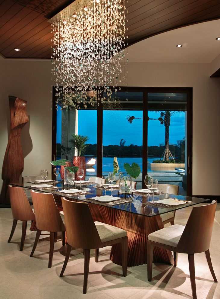 Expensive Chandeliers   Tropical Dining Room  and Crystal Dramatic Lighting Elephant Ear Glass Dining Table Glass Sliding Door Glass Vase Hanging Light Fixture Place Settings Stemware Tile Floor Waterfront Wood Ceiling Wood Sculpture