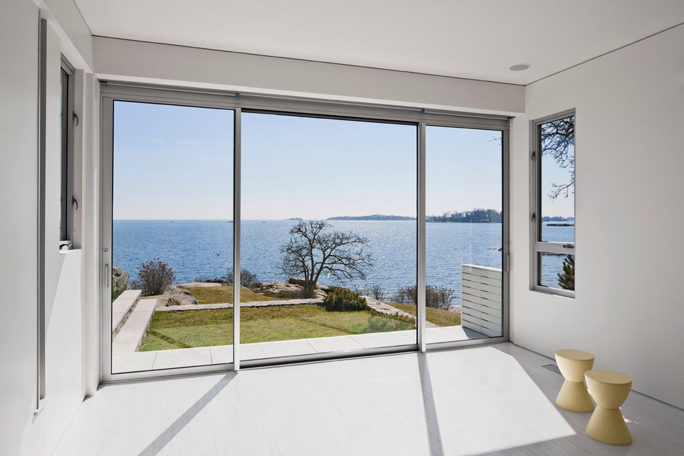 Exterior Door with Blinds Between Glass   Modern Home Gym  and Aluminum Windows Backyard Coastal Connecticut Grass Light Gray Molded Plastic Stool Shoreline Sliding Glass Doors Terrazzo Tile Floor Water View Waterfront Yoga Studio