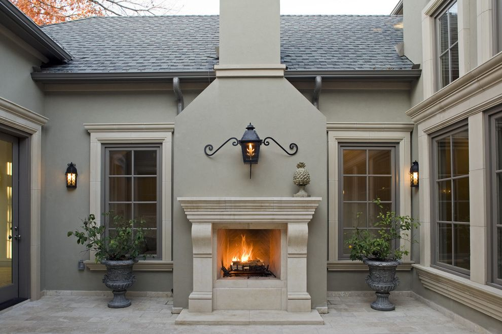 Exterior Paint Colors with Brown Roof with Mediterranean Patio  and Carved Stone Mantel Courtyard Glass Door Lantern Outdoor Fireplace Stone Trim Stucco Tile Floor Urns Wall Sconce