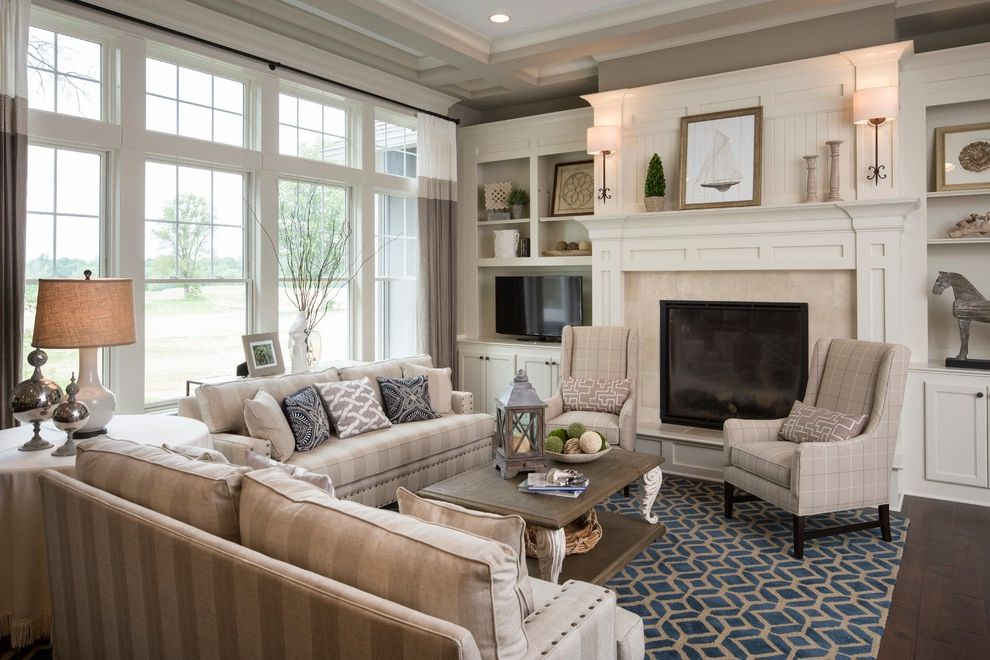 Family Leisure Indianapolis with Traditional Living Room Also Art Above Fireplace Beige Striped Sofa Blue Area Rug Built in Cabinets Clerestory Windows Coffered Ceiling Nailhead Trim Plaid Armchair Recessed Lighting Sailboat Art Wall Sconce