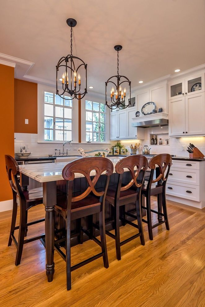 Faucets Galore with Traditional Kitchen  and Dark Wood Island Kitchen Island Light Orange Walls Pendant Lights Recessed Lighting Turned Legs Under Cabinet Lighting White Countertop Wood Bar Stools