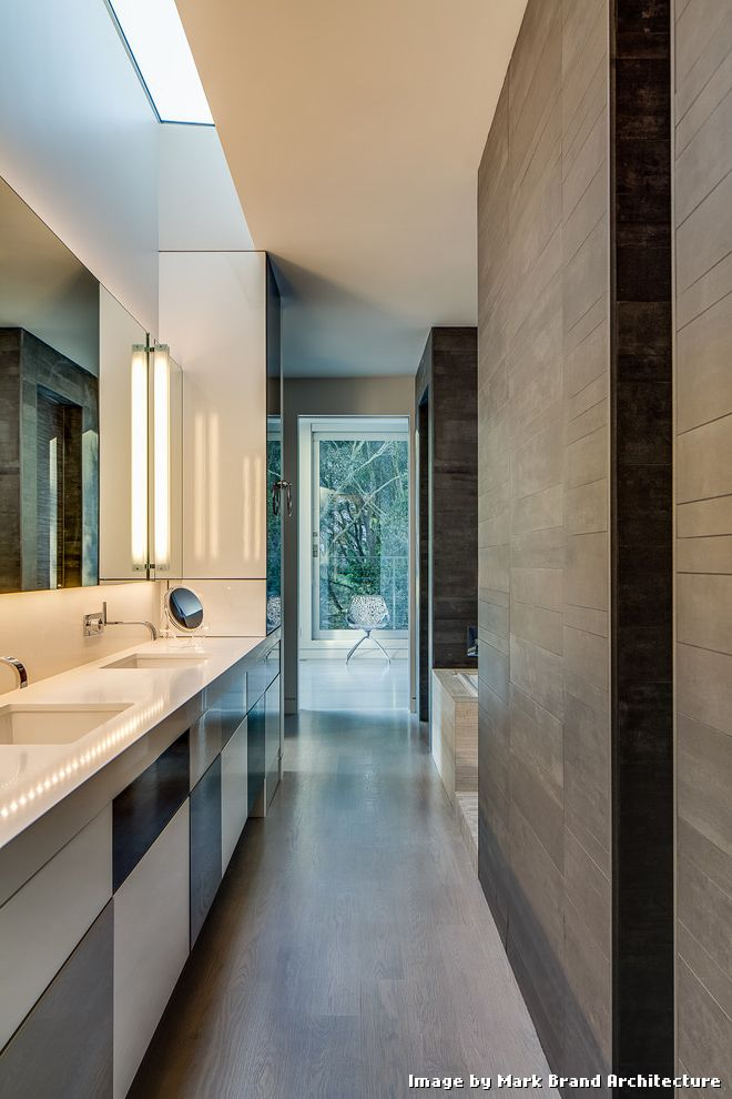 Floor Tiling Cost with Modern Bathroom and Double Sink Gray Floor Tile Makeup Mirror Minimalist Bathroom Open Doorway Rectangular Mirror Skylight Tub Deck Two Sinks Wall Sconces White Countertop