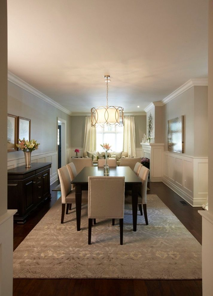 Formal Dining Room Sets for 10 with Traditional Dining Room  and Area Rug Crown Molding Dark Floor Drum Chandelier Sideboard Upholstered Dining Chairs Wainscoting White Wood Wood Flooring Wood Molding