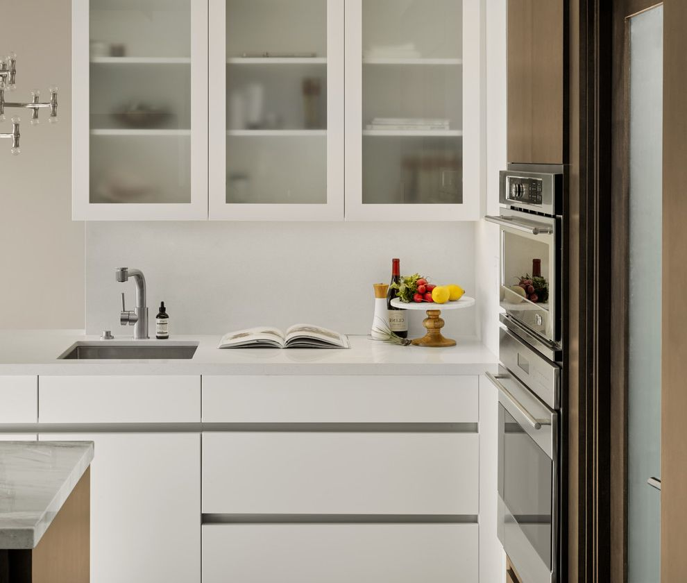 Frosted Glass Whiteboard with Contemporary Kitchen Also Brown Accents Clean Kitchen Clean Lines Frosted Glass Cabinets Kitchen Island Minimalist Kitchen Small Kitchen Small Sink Stainless Steel Sink Wall Oven White Countertop White Kitchen