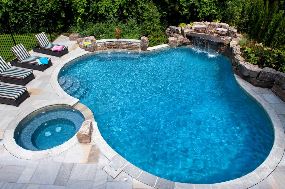 Gardner Pool Plastering with Traditional Pool  and Boulders Gray Tile Hot Tub Iron Fence Kidney Shaped Pool Patio Patio Furniture Rocks Round Hot Tub Stone Pool Surround Stone Wall Striped Lounge Chairs Waterfall