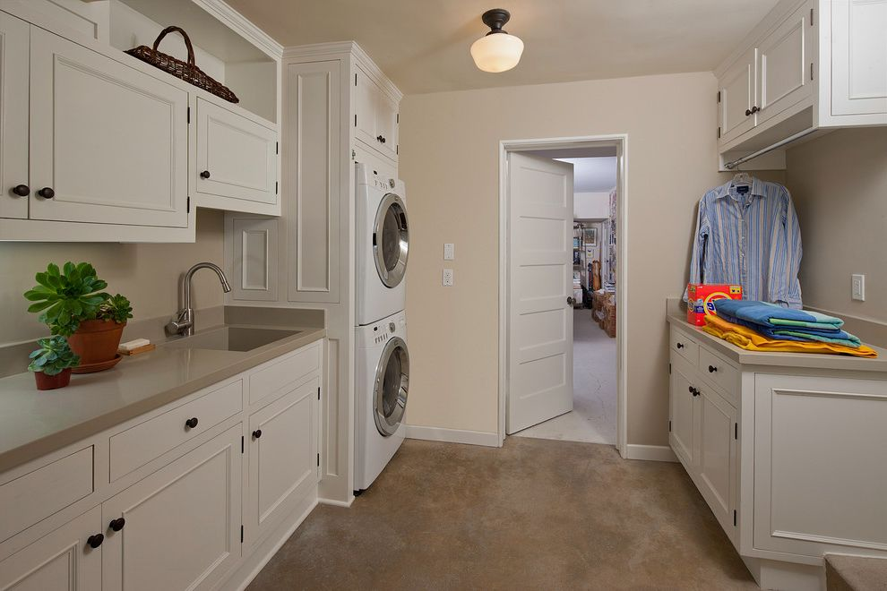 Gas Dryer vs Electric with Traditional Laundry Room Also Built in Storage Drying Rack Neutral Colors Schoolhouse Sconce Stackable Washer and Dryer Stacked Washer and Dryer Succulents White Cabinets