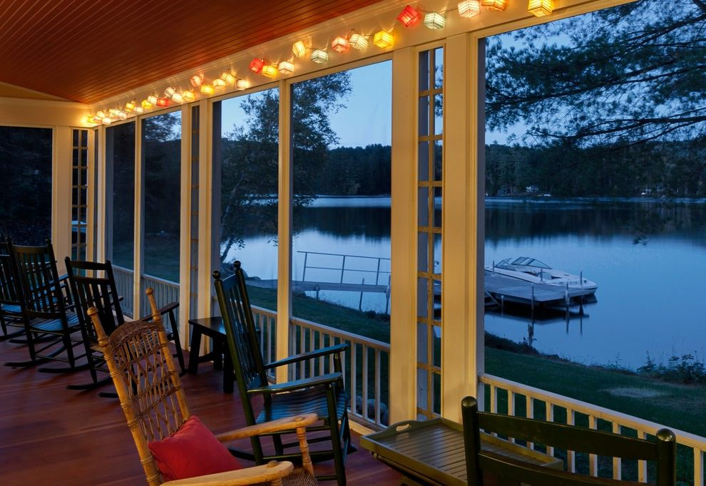 Gas Porch Light   Rustic Porch  and Decking Lake House Rocking Chairs Screened Porch String Lights Waterfront White Trim Wood Railing