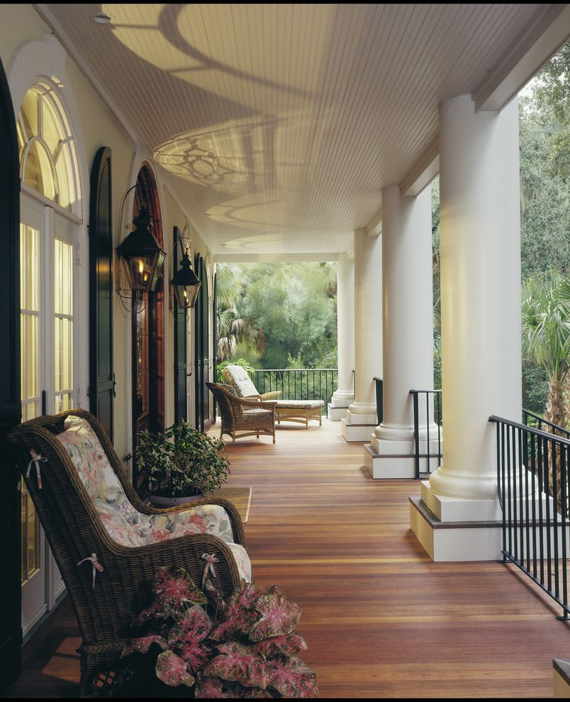Gas Porch Light with Traditional Balcony  and Arched Widow Beadboard Ceiing French Doors Front Porch Gas Lights Iron Railings Lanterns Large Columns Palm Tree Plants Shutters Southern Transom Wicker Rocker
