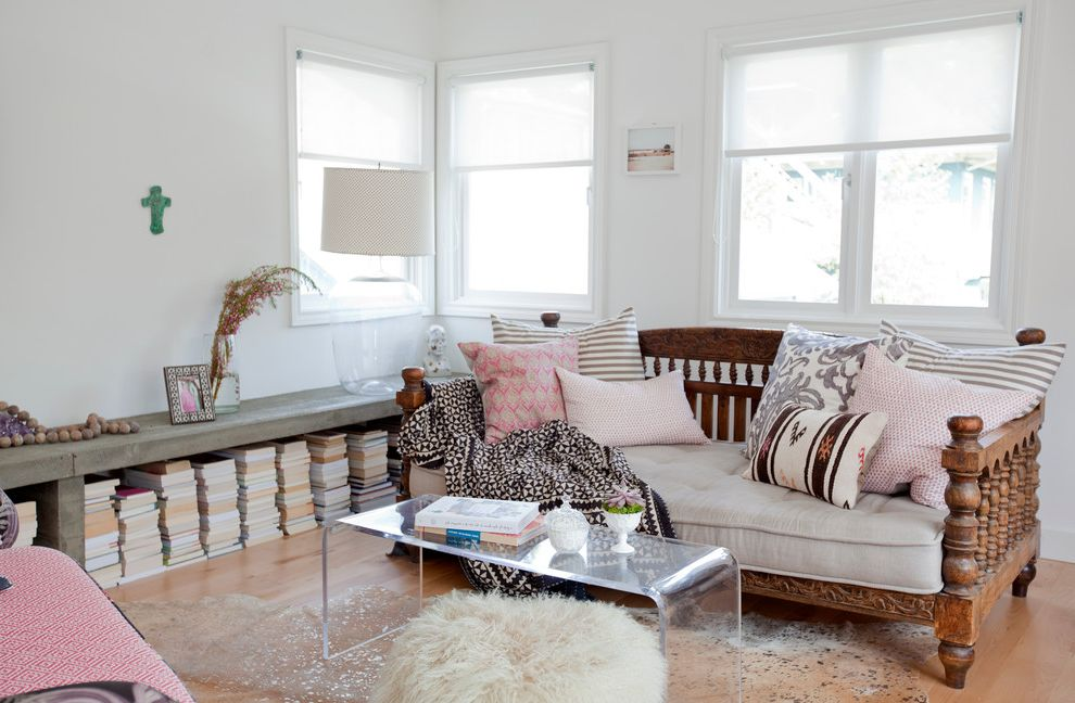 Ghost Coffee Table   Eclectic Living Room  and Carved Wood Bed Clear Acrylic Coffee Table Clear Coffee Table Corner Windows Daybed Decorative Pillows Pink Accents Pink Pillows Pouf Stacked Books Throw Pillows Wood Floors