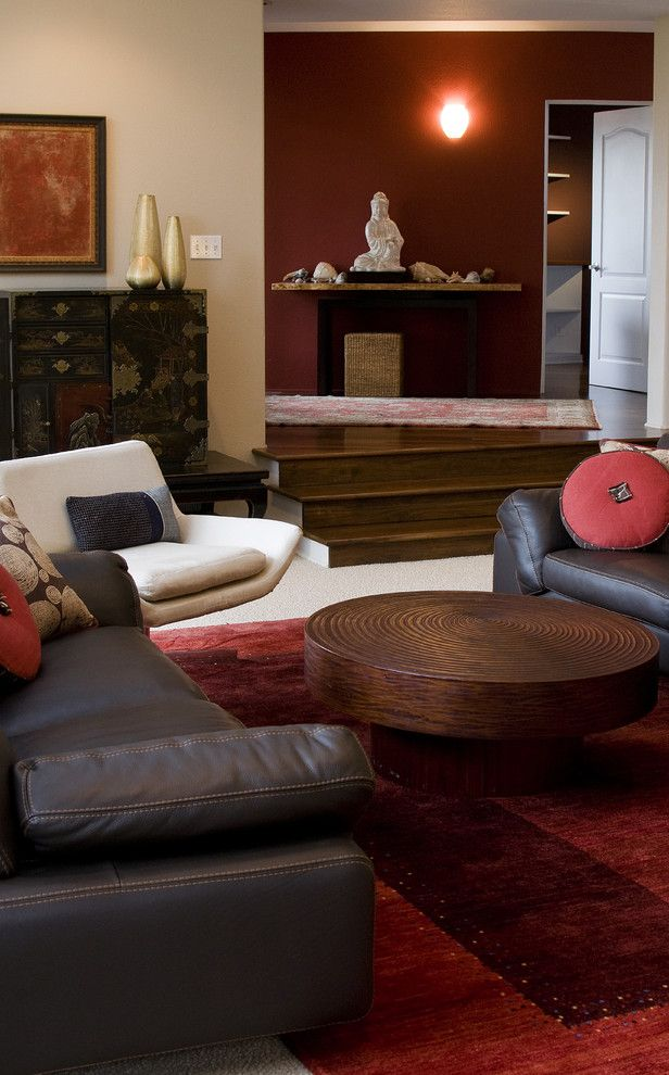 Ghost Coffee Table with Contemporary Living Room  and Area Rug Asian Beige Dark Stained Wood Floor Leather Couch Red Wall Round Coffee Table Sofa Wall Sconce White Trim