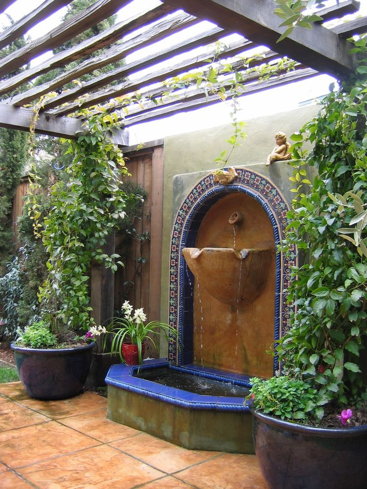 Golden Gate Villa Santa Cruz with Mediterranean Patio  and Accent Tiles Acid Stained Concrete Arbor Backyard Container Plants Fountain Patio Pergola Pond Potted Plants Tile Trellis Water Feature