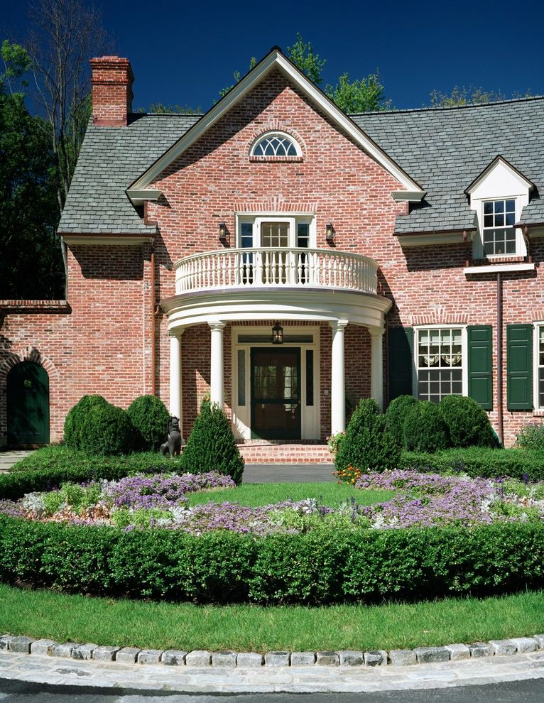 Grand Manor Roof with Traditional Exterior  and Brick Chimney Columns Dormer Windows Entry Front Door Green Shutters Muntins Planting Shrubs Shutters White Trim