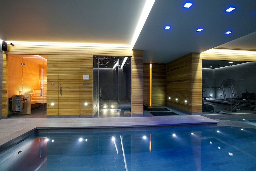 Grande Med Spa with Modern Pool  and Guncast Home Spa Indoor Gym Indoor Pool London Luxury Spa Area Pool Lighting Rectilinear Pool Sauna Steam Room Surrey Swimming Pool Design Underwater Lighting Wood Siding