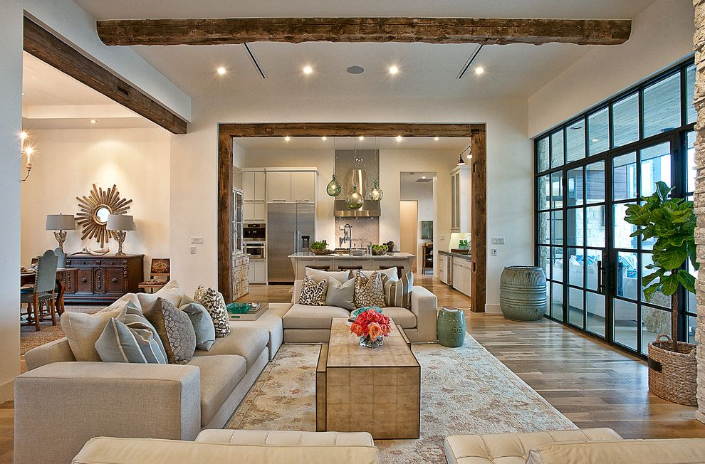 Great Finds and Designs   Transitional Living Room  and Area Rug Beige Firepace Patio Seating Area Sectional Slant Ceilings Stone Wall Tall Windows White Leather Tufted Upholstery Wood Beams Wood Floors