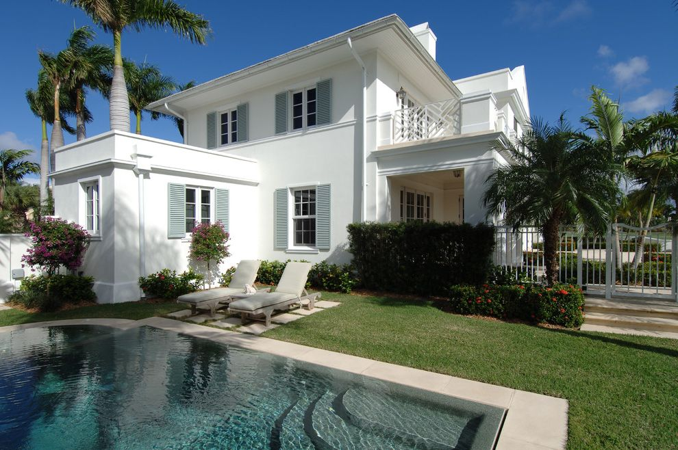 Grey House White Shutters with Tropical Exterior  and Balcony Cast Stone Concrete Pool Deck Grass Iron Gate Lawn Lounge Chairs Outdoor Seating Palm Trees Plantation Shutters Pool Shutters Stepping Stones White Stucco