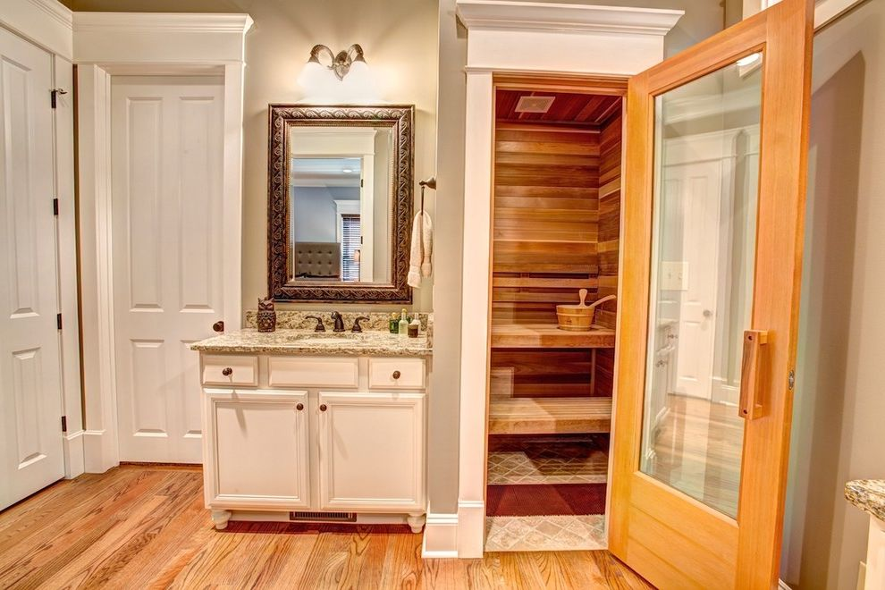 Gyms with a Sauna   Traditional Bathroom Also Framed Mirror Gerahmter Badezimmerspiegel Glass Door Hardwood Floor Marmor Waschtisch Neutral Colors Sauna Sauna Im Badezimmer Sconce Sink Spa Steam Room Vanity White Door Wood Paneling