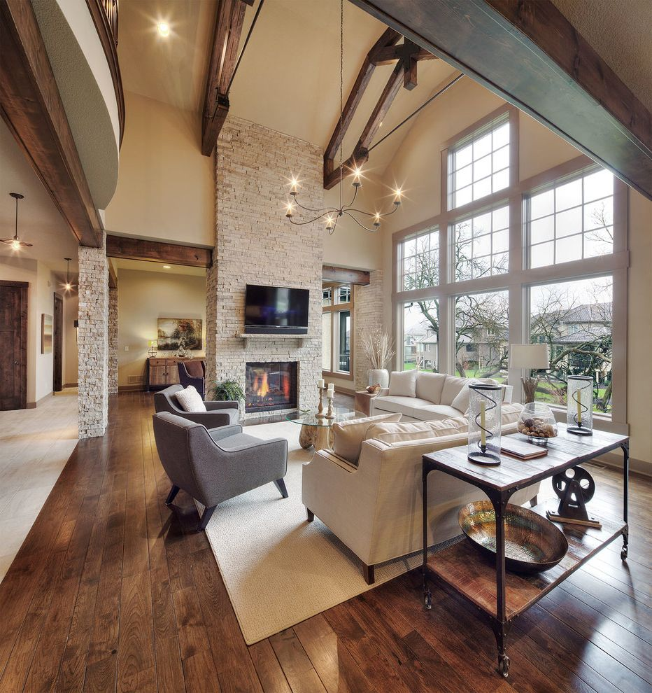 Hardwood Flooring Kansas City   Rustic Family Room  and Beige Sofa Dark Wood Beams Dark Wood Trusses Gray Armchair High Ceiling Stone Column