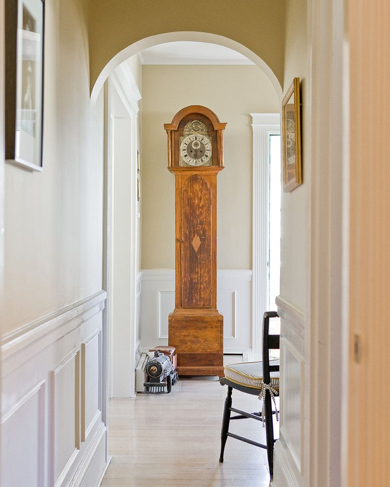 Herman Miller Clocks   Traditional Hall  and Antique Toy Train Arched Doorway Artwork Fluted Trim Frame and Panel Woodwork Grandfather Clock Seat Cushion Side Chair Wainscot White Painted Wood Wood Floor