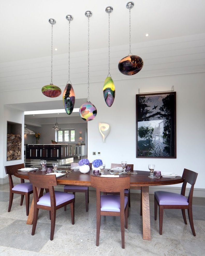 High Hat Lights   Traditional Dining Room  and Colorful Glass Pendants Dining Room Firewood Storage Framed Artwork Polished Gray Tiled Floor Purple Seat Cushions Recessed Lights Wall Sconce Wooden Dining Chairs Wooden Oval Dining Table